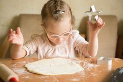 Happy girl with Down  syndrome bakes cookies Stock Photo