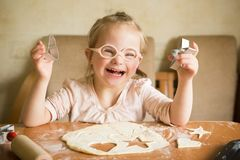 Happy girl with Down syndrome  bakes cookies. Happy girl with Down syndrome bakes cookies Stock Photo