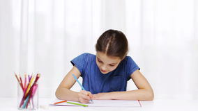 Happy girl drawing with colour pencils at home stock video