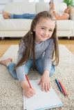 Happy girl drawing with her mother reading newspaper Stock Photography