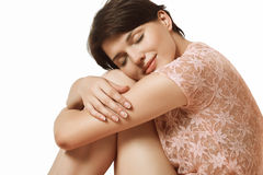 Happy girl dreams. Young and happy girl sitting on the floor and hugging her silky and tender feet Stock Photos