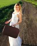 Happy girl in dress with retro suitcase, walking on lonely road Royalty Free Stock Photo