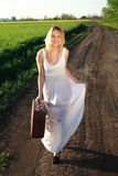 Happy girl in dress with retro suitcase, walking on lonely road. Beautiful blond girl in long white dress with suitcase at countryside, walking on lonely road Royalty Free Stock Images