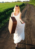 Happy girl in dress with retro suitcase, walking on lonely road Stock Photography