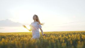 Happy girl in dress running in a green field of a young 4K stock footage