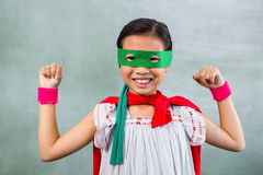 Happy girl dressed as superhero in classroom. Portrait of happy girl dressed as superhero in classroom Stock Photo