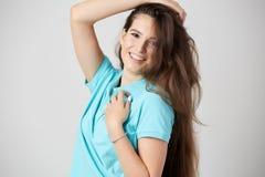 Happy girl dressed in light blue t-shirt smiles stock image