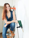 Happy girl with drill on stepladder Royalty Free Stock Images