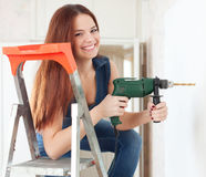 Happy girl drills hole in the wall Royalty Free Stock Images