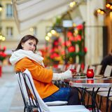 Happy girl drinking coffee in a Parisian cafe Royalty Free Stock Image