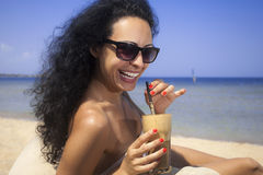 Happy girl drinking iced coffee on the beach Stock Image