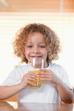 Happy girl drinking orange juice in the kitchen Stock Photos