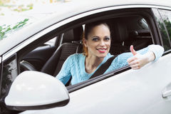 Happy girl driving a car and showing thumb up Royalty Free Stock Photo