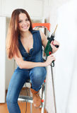 Happy girl in dungarees with drill Stock Photo