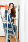 Happy girl in dungarees with drill Royalty Free Stock Photography