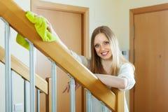 Happy  girl dusting stair railings Royalty Free Stock Photo