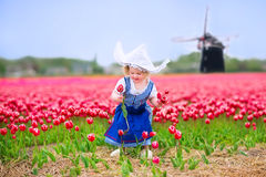 Happy girl in Dutch costume in tulips field with windmill. Adorable curly toddler girl wearing Dutch traditional national costume dress and hat playing in a Royalty Free Stock Photos
