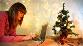 Smiling girl working on laptop on vacations. Happy girl earns money on holidays writing articles on laptop for Christmas. Young woman typing near decorated fir stock video footage