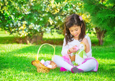 Happy girl in Easter holiday. Cute little girl playing Easter game, find colorful eggs and fed them a bunny toy, having fun in fresh green garden, happy spring stock photo