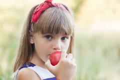 Happy girl eating an apple stock photo