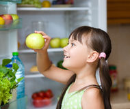 Happy girl eating apple standing near refrigerator Royalty Free Stock Image
