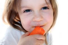 Happy girl eating carrot royalty free stock photos