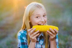 Happy girl eating healthy corn on the cob Royalty Free Stock Photography