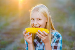 Happy girl eating healthy corn on the cob Royalty Free Stock Image