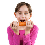 Happy girl eating a large carrot Royalty Free Stock Photography