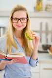 Happy girl eating sandwich and reading book Royalty Free Stock Photos