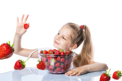 Happy girl eating strawberries Royalty Free Stock Image