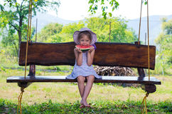 Happy girl eating a watermelon sitting on a swing, summer photo. Royalty Free Stock Photos