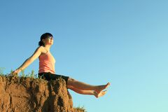 Happy girl on the edge with legs outstretched Royalty Free Stock Photography