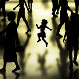 Happy girl. Editable vector silhouette of a young girl skipping in a crowded hall made using a gradient mesh Stock Photos