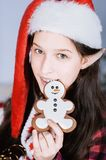 Happy girl with elf ears holds in his hands gingerbread. snowman. The concept of Christmas celebration and cooking. Happy girl with elf ears holds in his hands royalty free stock photo