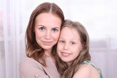 Happy girl embraces her young mother near window Royalty Free Stock Image