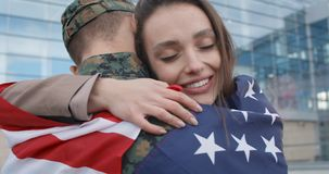 Happy girl embracing military boyfriend covered with american flag. Close up of happy girl embracing military husband covered with american flag. Smiling wife stock footage