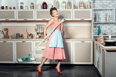 Happy girl engaged in cleaning the kitchen. Stock Image