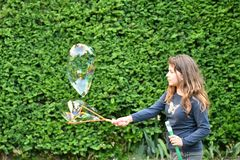 Young girl plays with a soap bubbles in a garden stock images
