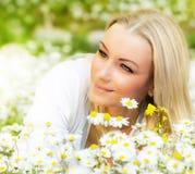 Happy girl enjoying daisy flower field stock image