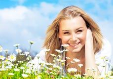Happy girl enjoying daisy flower field Stock Images