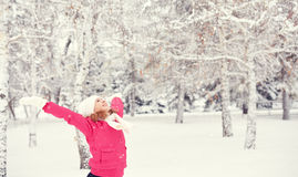 Happy girl enjoying life and throws snow at winter outdoors Stock Photo