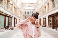 Happy girl enjoying listening to music on a city street Stock Photography