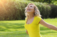 Happy girl enjoying the Nature on green grass.  Beautiful young woman smiling with arms outstretched Stock Photo