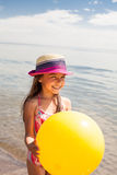 Happy girl enjoying sunny day at the beach. Holds a big yellow ball Stock Photography