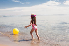 Happy girl enjoying sunny day at the beach. Running with balloon Stock Photo