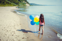 Happy girl enjoying sunny day at the beach. Running with balloons Royalty Free Stock Images