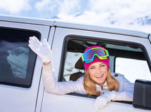 Happy girl enjoying winter sports. Cheerful portrait of a woman sitting in the car and wearing ski mask, arrived to alpine ski resort, tourist travel on Royalty Free Stock Images