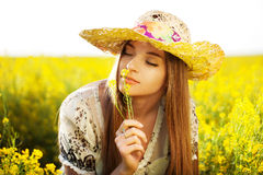 Happy girl enjoys the smell of a flower Royalty Free Stock Image