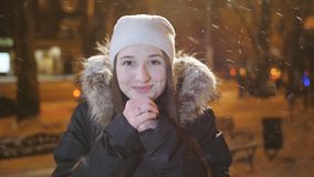 Portrait of girl in evening winter city. A girl rejoices at the falling snow and warming his hands. stock video